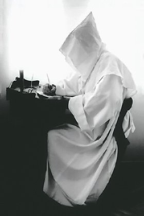 White monk sitting and writing